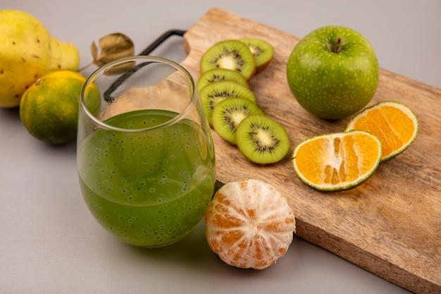 Bovenaanzicht van heerlijke gehakte kiwiplakken met mandarijn en appel op een houten keukenbord met vers kiwisap