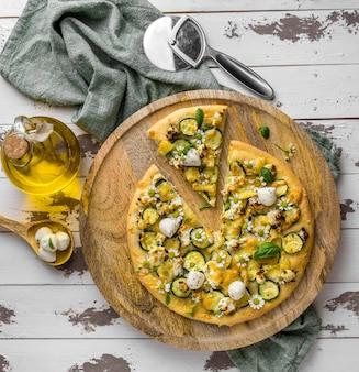 Bovenaanzicht van heerlijke gekookte pizza met kamille bloemen en olie