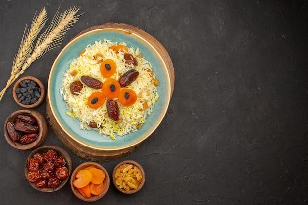 Bovenaanzicht van heerlijke gekookte plov rijst met verschillende rozijnen binnen plaat op donkere ondergrond