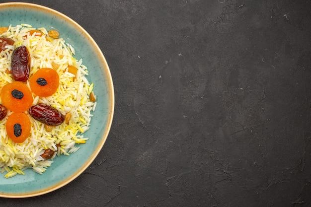 Bovenaanzicht van heerlijke gekookte plov rijst met verschillende rozijnen in plaat op donkergrijs oppervlak