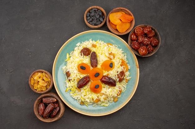 Bovenaanzicht van heerlijke gekookte plov-rijst met verschillende rozijnen in plaat op het grijze oppervlak
