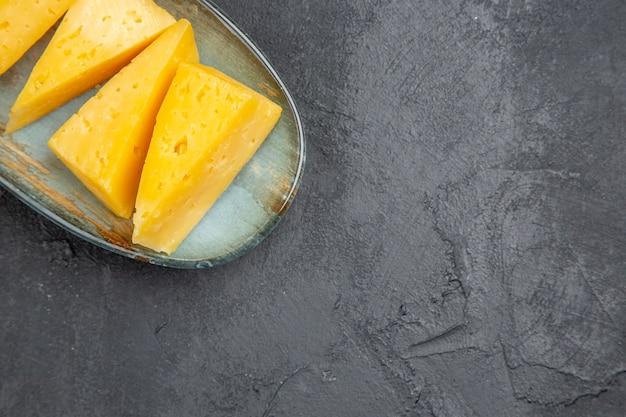 Bovenaanzicht van heerlijke gele gesneden kaas op een blauw bord aan de rechterkant op zwarte achtergrond