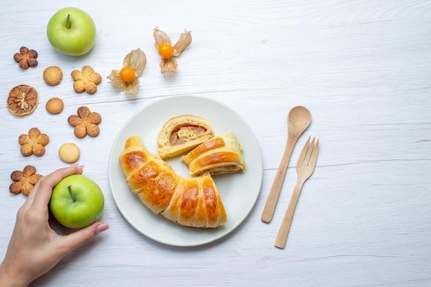 Bovenaanzicht van heerlijke gesneden gebakjes in plaat met vulling samen met appels en koekjes op wit bureau, gebak cookie koekje zoete suiker