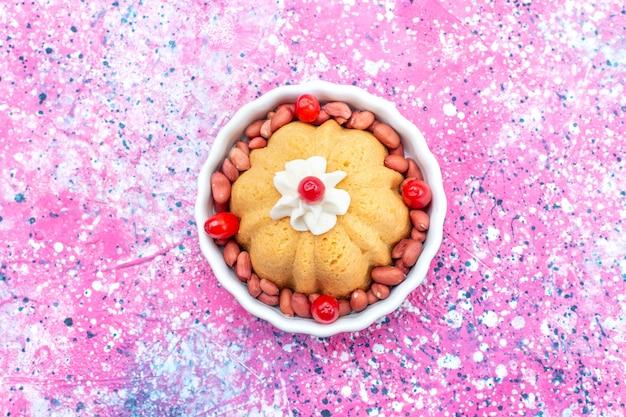 Bovenaanzicht van heerlijke gewone cake met room en verse pinda's op helder