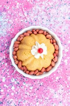 Bovenaanzicht van heerlijke gewone cake met room en verse pinda's op heldere, zoete suikernoot van het cakekoekje