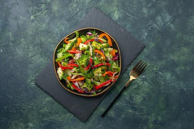 Bovenaanzicht van heerlijke groentesalade met verschillende ingrediënten op zwarte snijplank