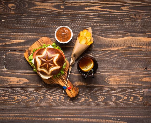 Bovenaanzicht van heerlijke hamburger met groenten op een houten achtergrond.