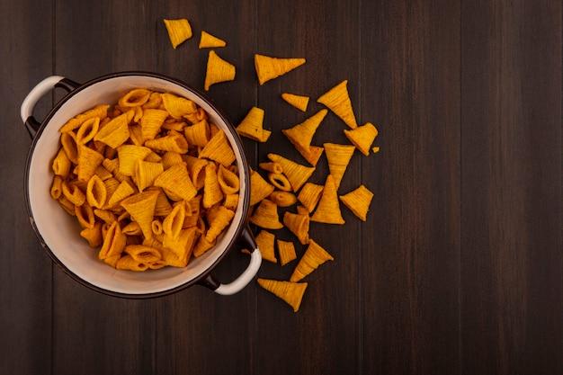 Bovenaanzicht van heerlijke kegelvorm gebakken maïs snacks op een kom op een houten tafel met kopie ruimte