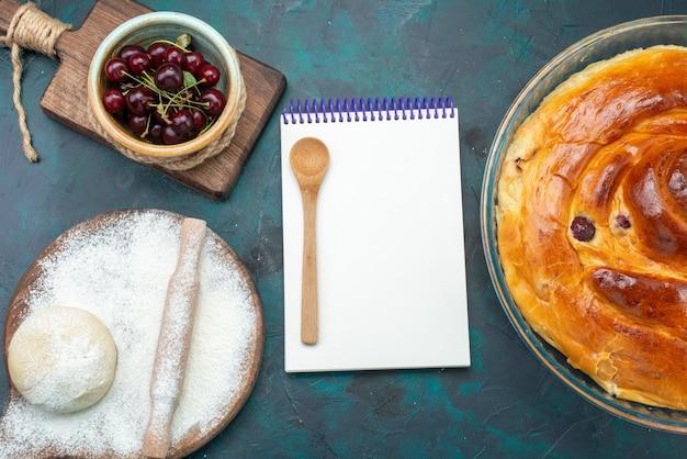 Bovenaanzicht van heerlijke kersentaart met kladblok-deegkersen op donkerblauw, taartcake zoete suiker bakken