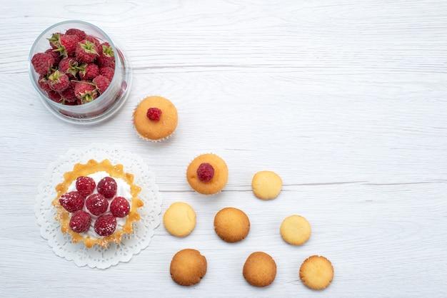 Bovenaanzicht van heerlijke kleine cake met frambozen samen met aardbeien en koekjes op licht, cake koekje zoete bes