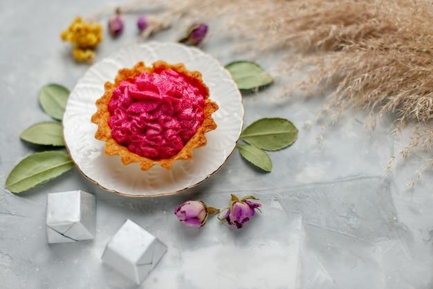 Bovenaanzicht van heerlijke kleine cake met roze room en kleine chocolaatjes op licht, cake zoete bak room thee snoep