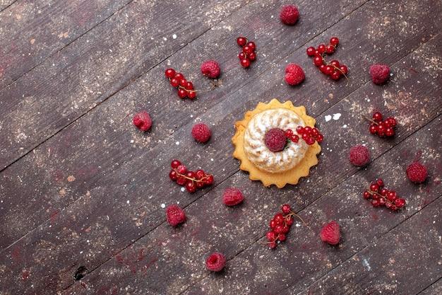 Bovenaanzicht van heerlijke kleine cake met suikerpoeder samen met frambozen, veenbessen langs bruin, bessenfruitcake