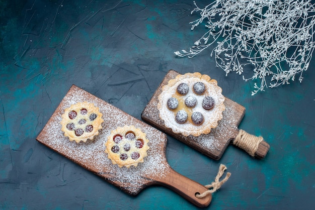 Bovenaanzicht van heerlijke kleine cakes suiker in poedervorm met fruit op donkerblauw bureau, cakekoekje zoete suiker