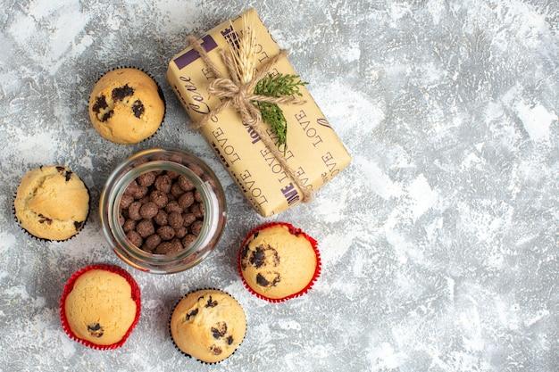 Bovenaanzicht van heerlijke kleine cupcakes en chocolade in een glazen pot naast kerstcadeau aan de rechterkant op ijsoppervlak