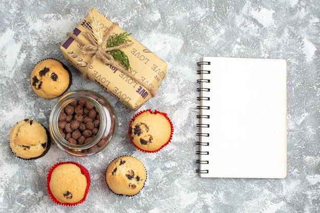 Bovenaanzicht van heerlijke kleine cupcakes en chocolade in een glazen pot naast kerstcadeau en gesloten notitieboekje op ijsoppervlak