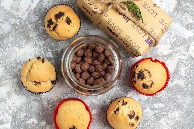 Bovenaanzicht van heerlijke kleine cupcakes en chocolade in een glazen pot naast kerstcadeau op ijsoppervlak