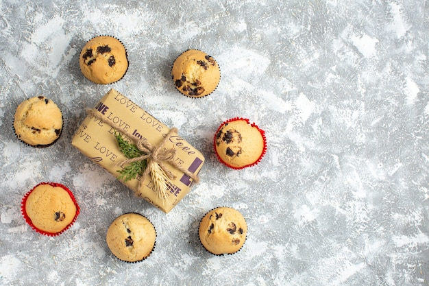 Bovenaanzicht van heerlijke kleine cupcakes met chocolade rond cadeau met liefdesinscriptie aan de linkerkant op ijsoppervlak