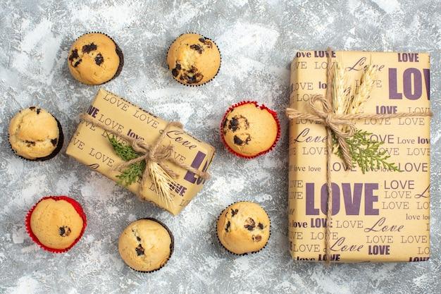 Bovenaanzicht van heerlijke kleine cupcakes met chocolade rond cadeau met liefdesinscriptie en groot cadeau op ijsoppervlak