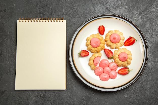 Bovenaanzicht van heerlijke kleine koekjes met roze crème binnen plaat op grijs oppervlak