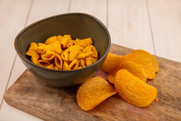 Bovenaanzicht van heerlijke knapperige kegelvorm maïs snacks op een kom op een houten keukenbord op een beige houten tafel