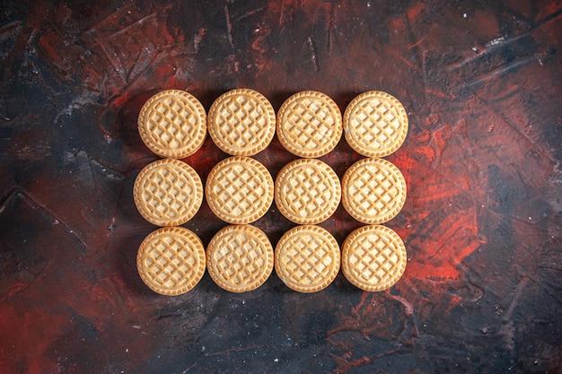 Bovenaanzicht van heerlijke koekjes gerangschikt in rijen op mix kleuren achtergrond met vrije ruimte