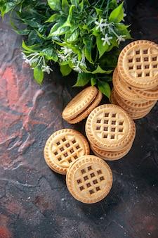 Bovenaanzicht van heerlijke koekjes gerangschikt in verschillende vormen en bloem op mix kleuren achtergrond met vrije ruimte