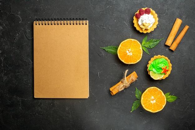 Bovenaanzicht van heerlijke koekjes, kaneellimoenen en half gesneden sinaasappels met bladeren en notitieboekje op donkere achtergrond