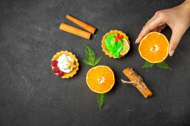 Bovenaanzicht van heerlijke koekjes, kaneellimoenen en half gesneden sinaasappels met bladeren op een donkere achtergrond
