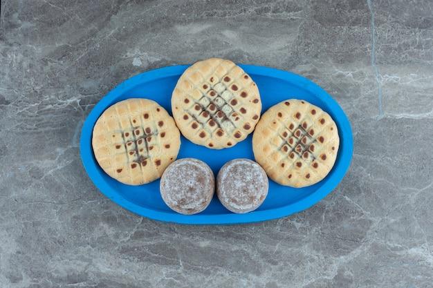 Bovenaanzicht van heerlijke koekjes op blauwe houten plaat.