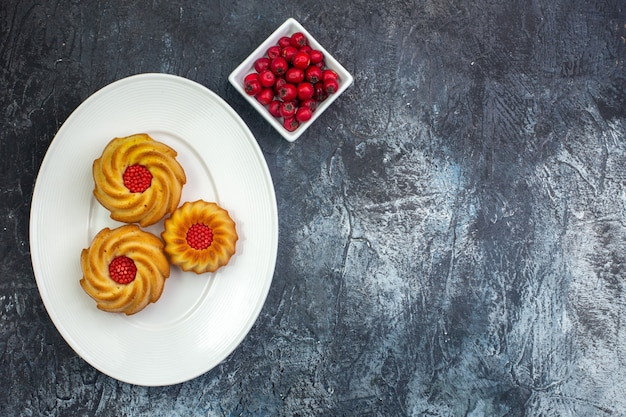 Bovenaanzicht van heerlijke koekjes op een witte plaat en cornel in kom aan de rechterkant op donkere ondergrond