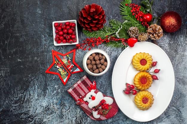 Bovenaanzicht van heerlijke koekjes op een witte plaat en cornell-chocolade in kommen dennentakken aan de linkerkant op een donkere ondergrond