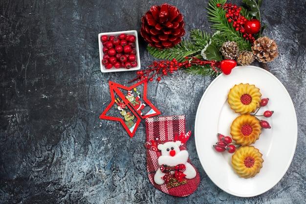 Bovenaanzicht van heerlijke koekjes op een witte plaat en cornell in een kom dennentakken op een donkere ondergrond