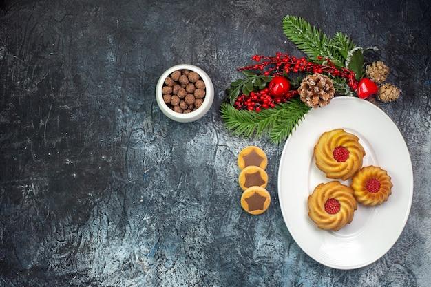 Bovenaanzicht van heerlijke koekjes op een witte plaat kerstmuts en chocolade in een kom op een donkere ondergrond
