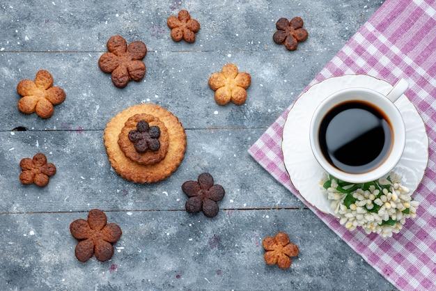 Bovenaanzicht van heerlijke koekjes zoet met kopje koffie de grijze, zoete koekjes suiker koekjes