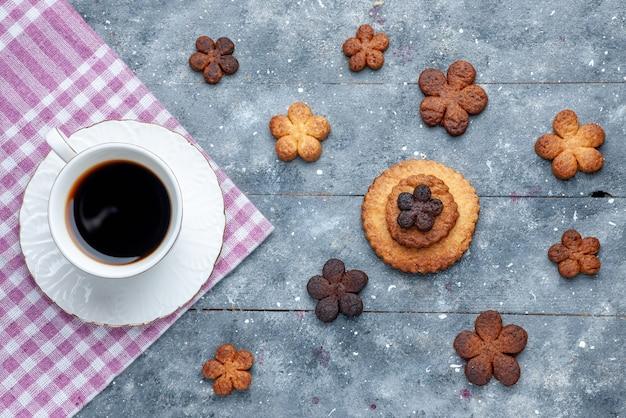 Bovenaanzicht van heerlijke koekjes zoet met kopje koffie de houten grijze, zoete koekjes suiker koekjes