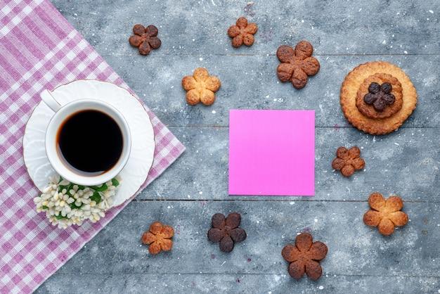 Bovenaanzicht van heerlijke koekjes zoet met kopje koffie het grijze rustieke bureau, koekjes suiker koekje zoet