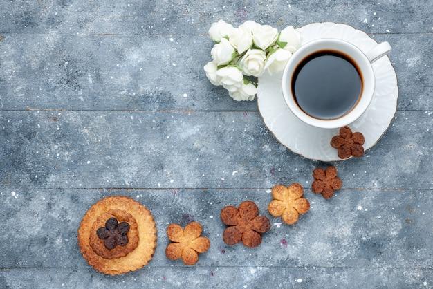 Bovenaanzicht van heerlijke koekjes zoet met kopje koffie op grijs bureau, koekjes suiker koekje zoet