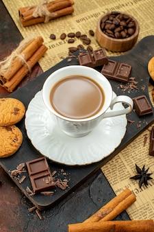 Bovenaanzicht van heerlijke koffie in een witte kop op een houten snijplank op een oude krant cookies, kaneel limoenen chocoladerepen