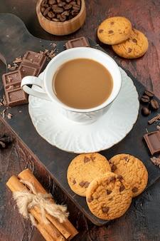 Bovenaanzicht van heerlijke koffie in witte kop op houten snijplank cookies kaneel limoenen chocoladerepen