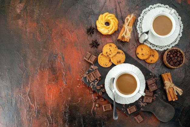 Bovenaanzicht van heerlijke koffie in witte kopjes op houten snijplank koekjes kaneel limoenen chocoladerepen aan de linkerkant op gemengde kleur achtergrond