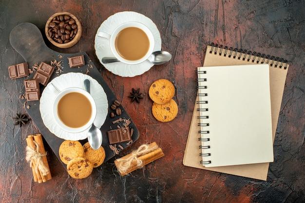 Bovenaanzicht van heerlijke koffie in witte kopjes op houten snijplank koekjes, kaneel limoenen, chocoladerepen, spiraalvormige notitieboekjes