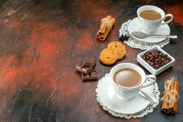 Bovenaanzicht van heerlijke koffie in witte kopjes op servetten, koekjes, kaneellimoenen, chocoladerepen aan de linkerkant op een gemengde kleurachtergrond