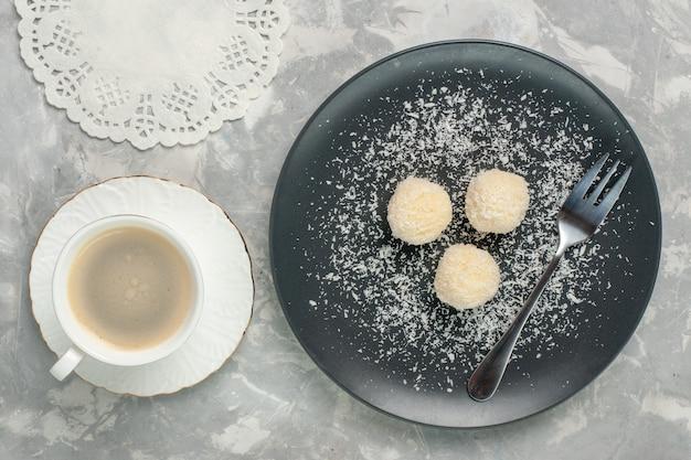 Bovenaanzicht van heerlijke kokos snoepjes met koffie op witte ondergrond