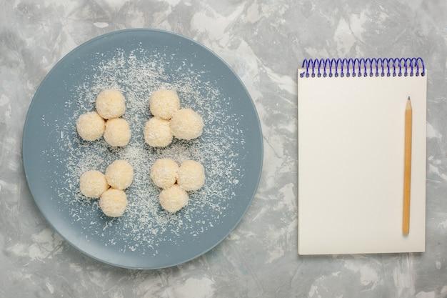 Bovenaanzicht van heerlijke kokosnoot snoepjes in blauw bord met kladblok op wit oppervlak