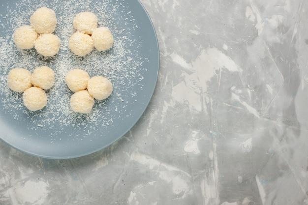 Bovenaanzicht van heerlijke kokosnoot snoepjes in blauw bord op witte ondergrond