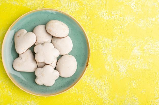 Bovenaanzicht van heerlijke lekkere koekjes in plaat op het gele oppervlak