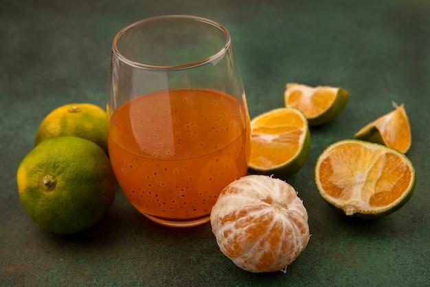 Bovenaanzicht van heerlijke mandarijnen met vers vruchtensap in een glas
