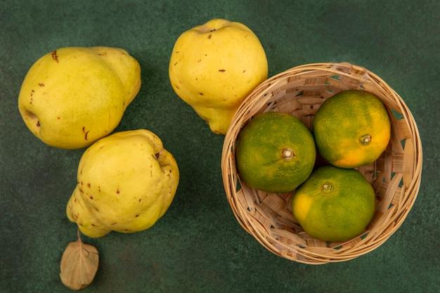 Bovenaanzicht van heerlijke mandarijnen op een emmer met kweeperen