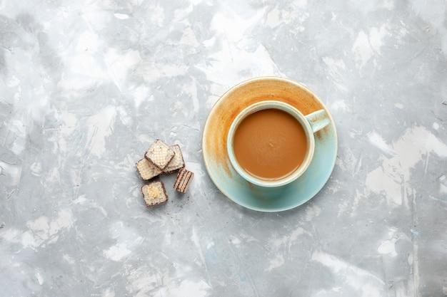 Bovenaanzicht van heerlijke melkkoffie met wafels op wit bureau, zoete suiker drink melk espresso