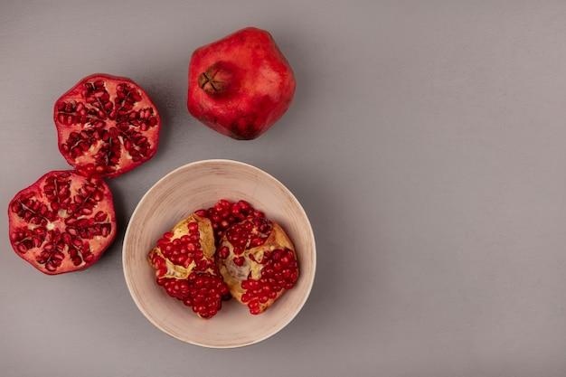 Bovenaanzicht van heerlijke open granaatappels met zaden op een kom met kopie ruimte